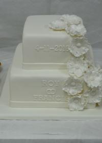 vierkante bruidstaart met fantasiebloemen en cupcakes